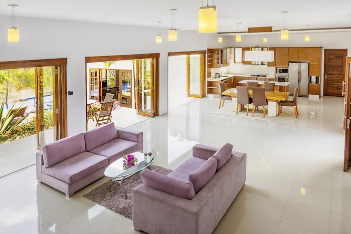 cuisine ouverte en bois, salle à manger vaec table en bois et chaises grises, salon canapé et tapis mauve, table minimaliste en verre, suspensions originales