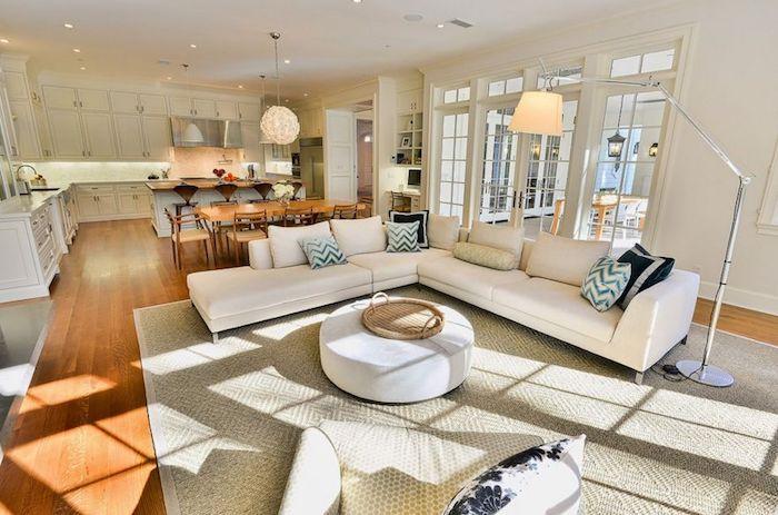 separation cuisine salon par une chaise salle à manger en bois, facade meuble cuisine bois blanc, canapé d angle blanc, tapis gris et table ronde minimaliste ronde, tapis gris et beige