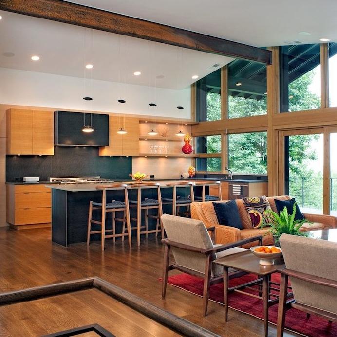 cuisine avec bar gris anthracite, facade meuble cuisine en bois, credence grise, chaises en bois et tissu noir, poutre apparente, salon avec canapé orange, chaises en bois et tapis rouge qui donne sur une terrasse végétalisée