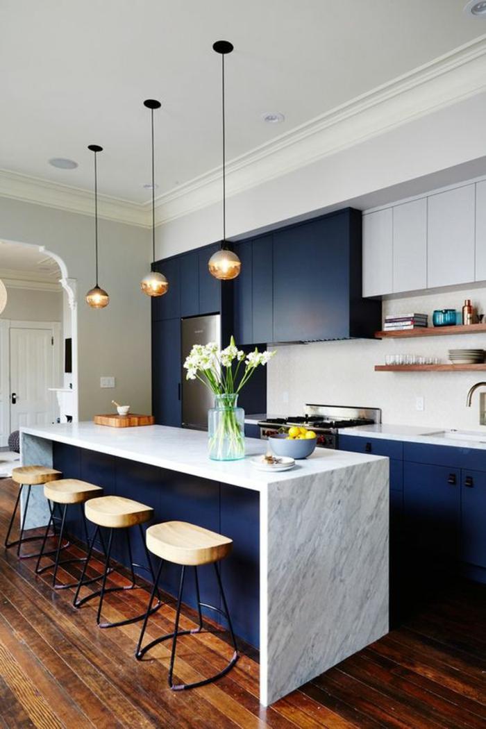 meuble bleu canard, îlot en blanc et bleu canard, trois luminaires en forme de boules en verre suspendus, quatre tabourets de bar en bois clair et en métal noir, parquet en marron foncé et en beige