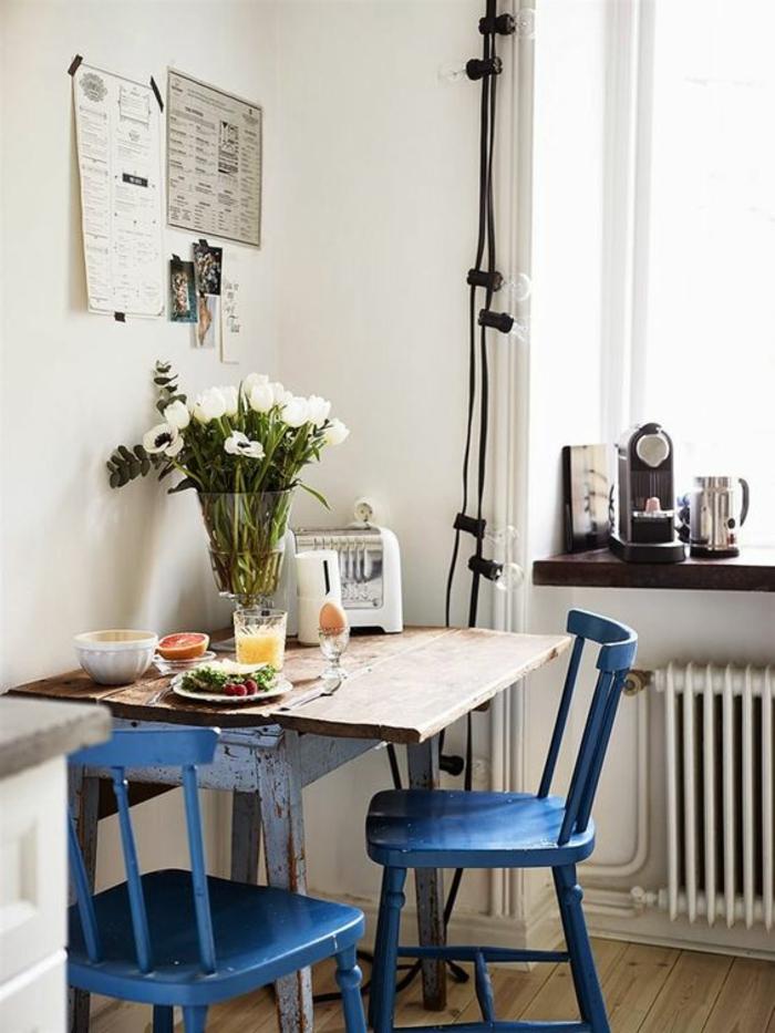 deco bleu canard, meuble bleu canard, petite table carrée en bois rude, murs blancs, guirlande lumineuse avec des ampoules autour de la fenêtre