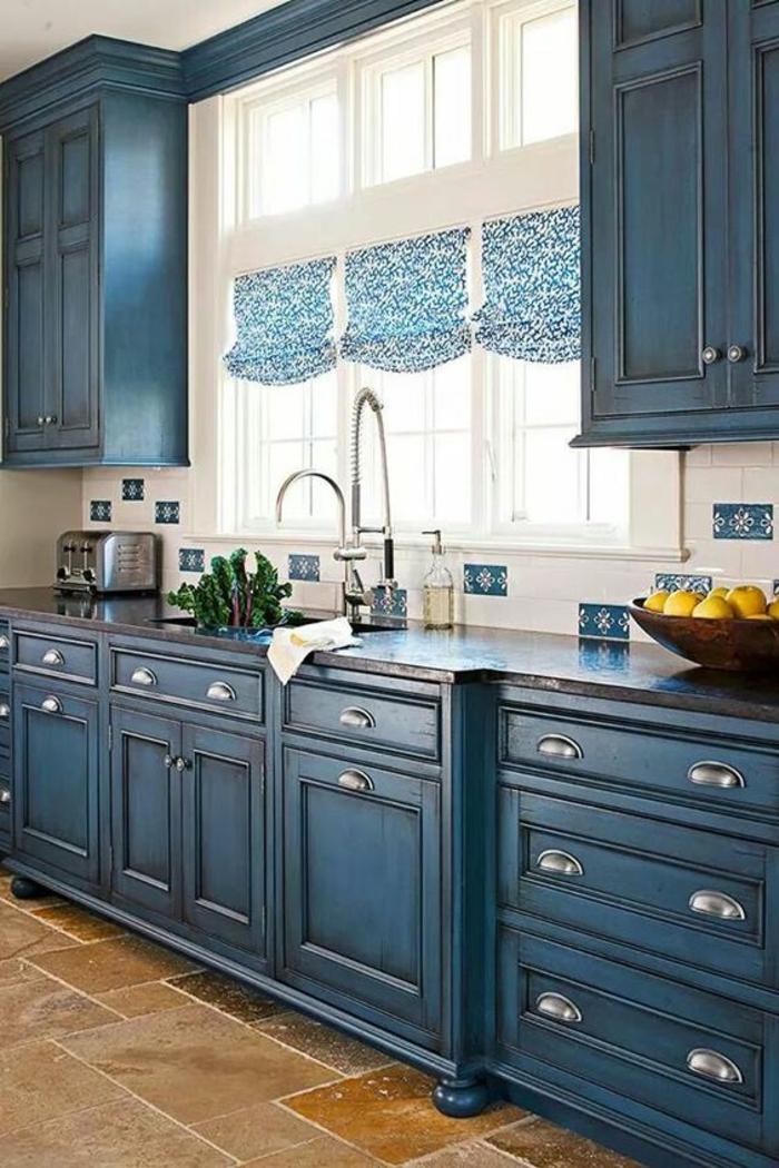 cuisine bleu, meuble bleu canard, des rideaux en bleu et blanc drapés, cadre des fenêtres blancs, carrelage en beige et marron clair, style d' ameublement classique