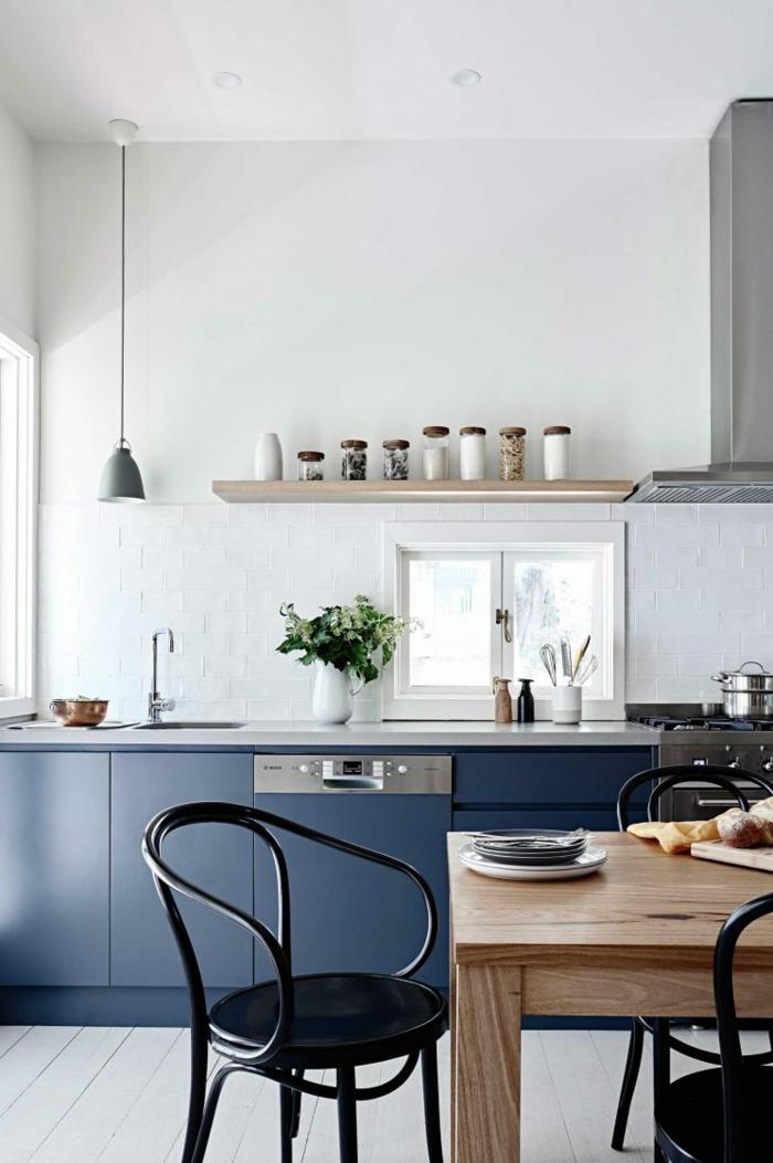 cuisine bleu nuit avec des chaises noires autour de la table en bois clair, aspirateur en inox, étagère en bois clair au-dessus du meuble du lavabo, carrelage blanc lisse