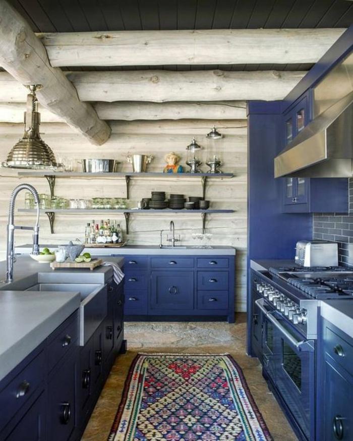 meuble bleu canard, poutres au plafond en couleur grise, murs aux revêtements de bois PVC gris, meuble bleu canard, tapis rectangulaire en style ethno avec des couleurs vives