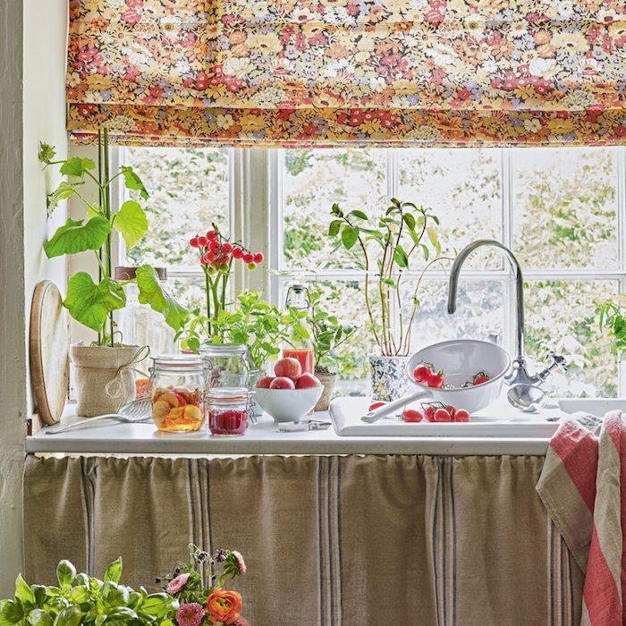 cuisine ancienne, decoration campagne avec plan de travail blanc, voilage à imprimé floral, style shabby chic, fleurs et fruits frais