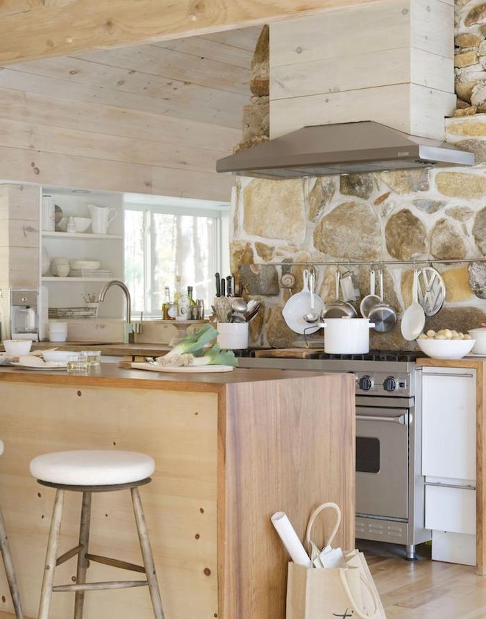 cuisine campagnarde en bois, avec mur en pierre, electromenager inox, poutres apparentes et murs habillés de lambris