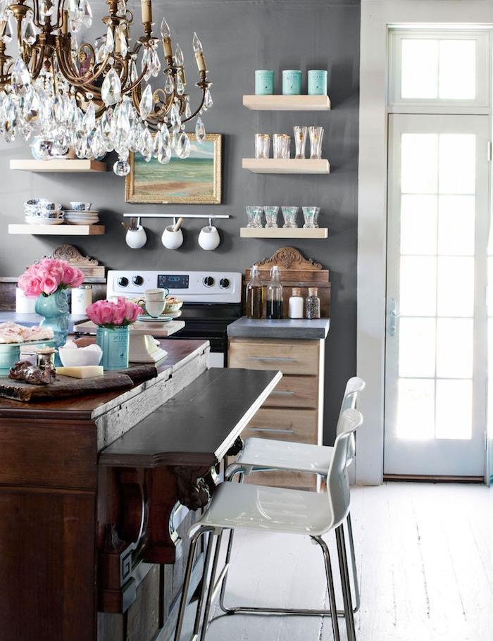 campagne decoration cuisine avec mur gris, décoré d etagres bois avec vaisselle, comptoir bois brut et lustre baroque, chaises blanches