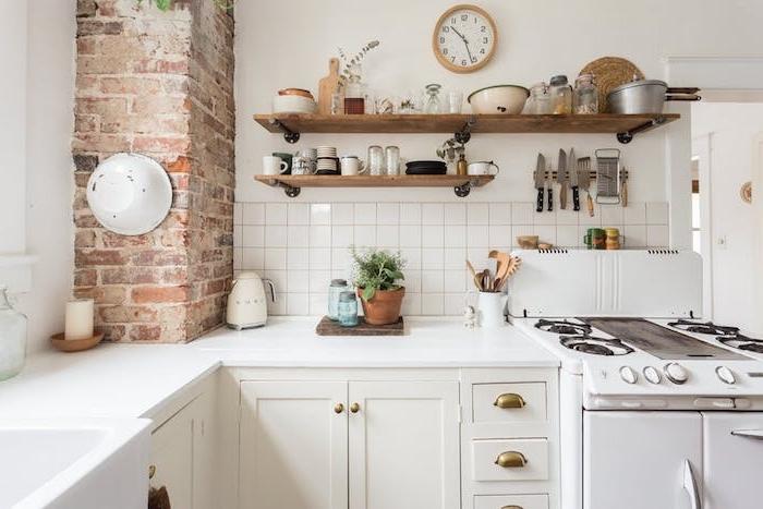 cuisine campagnarde avec mur en briques, facade meuble et plan de travail blanc, etagere en bois rustique avec vaisselle exposée