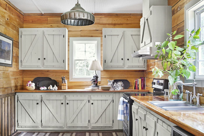 cuisine style campagne avec murs en lambris bois, facade cuisine et placards bois repeints en blanc, tapis gris, suspension grise, deco chalet, ferme