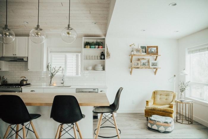 design scandinave, étagère murale en bois avec cadres photos en bois clair, fauteuil en tissu beige avec dos boutonné