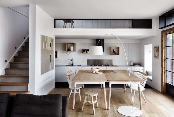 deco scandinave, cuisine ouverte vers le salon avec salle à manger, lampe sur pied blanche, décoration murale en bois avec statuette oiseau
