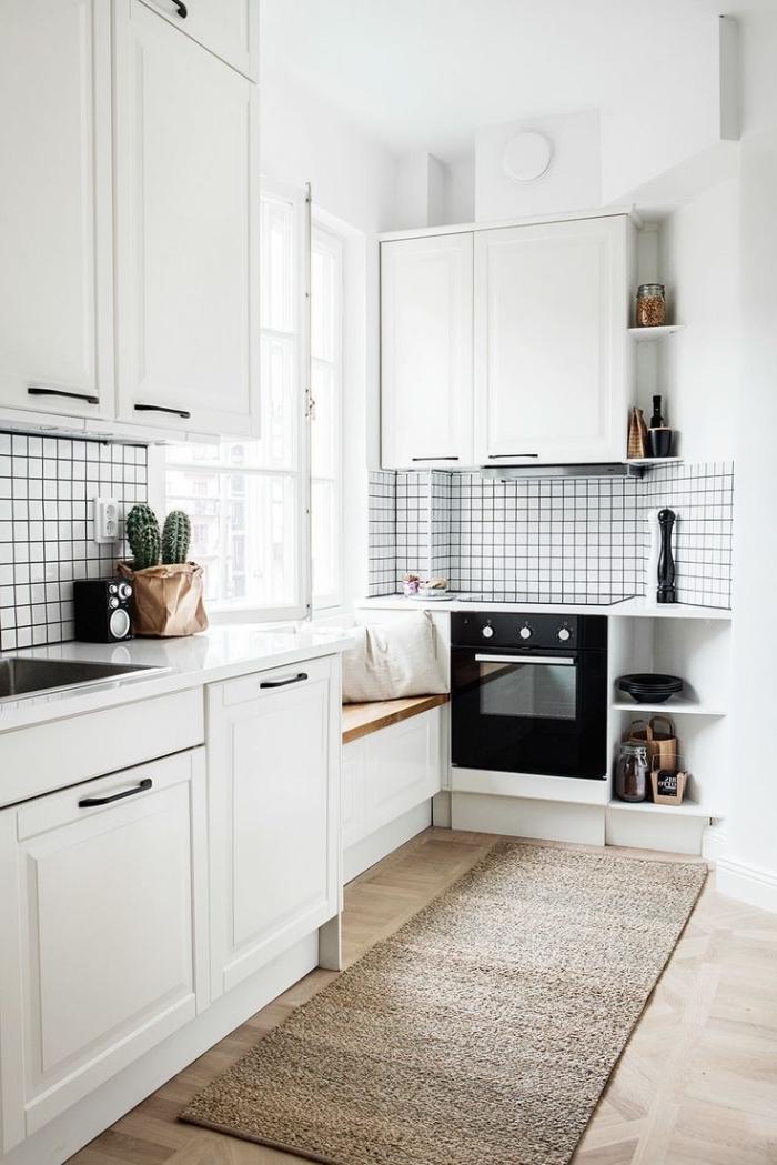 déco scandinave, banc en bois et blanc avec housses blanches au-dessous de la fenêtre, four noire dans cuisine blanche