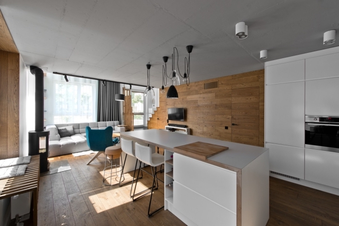 rideau scandinave long en gris anthracite, cheminée moderne noire dans la cuisine, meubles de cuisine blancs sans poignées