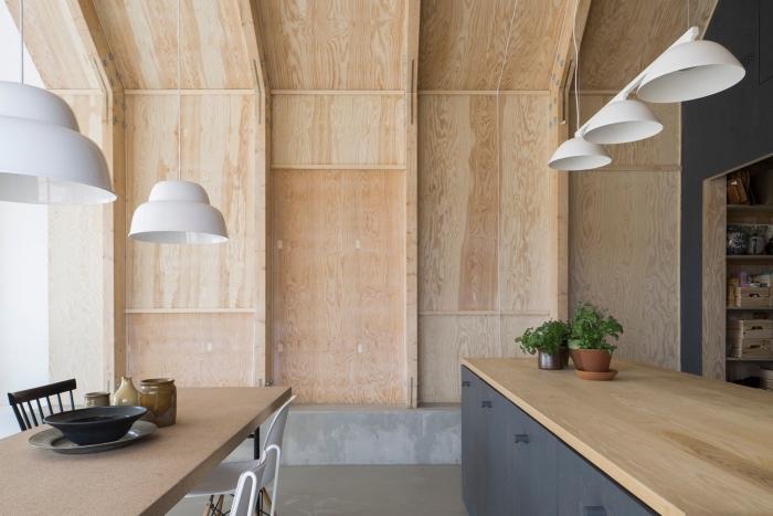 meuble scandinave, table à manger en beige avec chaises en blanc et noir, ilot central avec comptoir en bois clair et armoires en gris anthracite