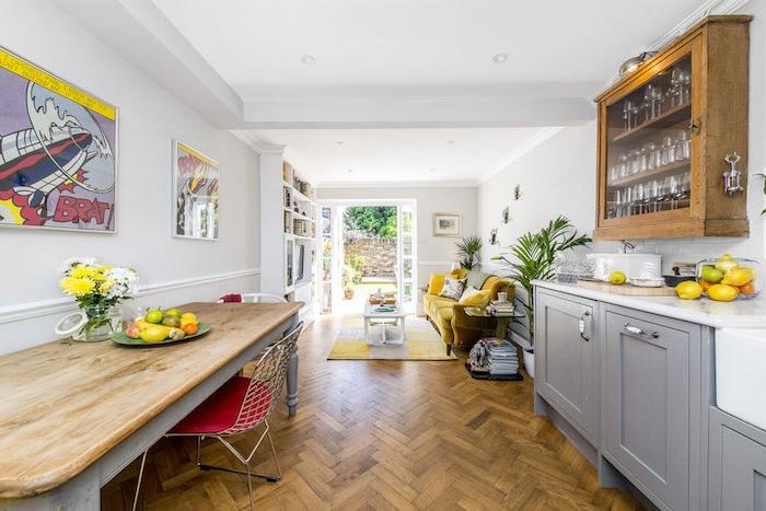 comment aménager une cuisine en longueur, facade meuble cuisine gris, table grise avec plateau en bois, revetement en parquet bois nature, vaisselier bois, canapé jaune et bibliothèque blanche dans le salon