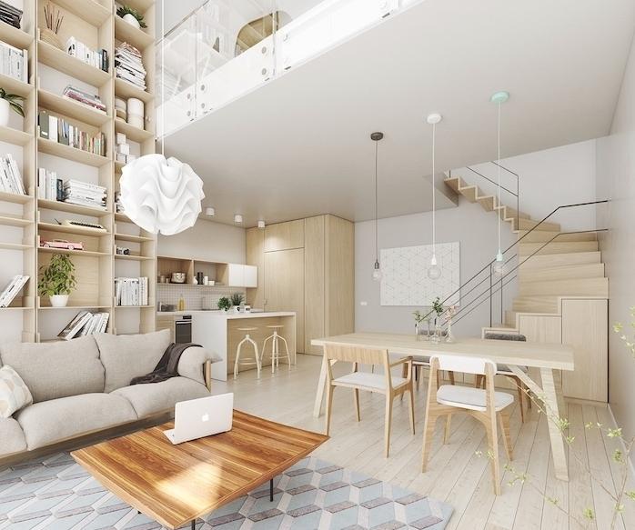 cuisine ouverte style scandinave en bois, meubles et parquet en bois, salon avec grande bibliotheque, canapé gris et table en bois, tapis à motifs géométriques