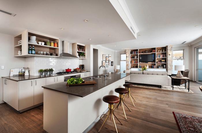 cuisine ouverte sur salon avec meuble blanc et etageres ouvertes blanches, bar blanc avec plan de travail gris, tabourets en cuir et metal, salon avec canapé gris et meuble tv bibliotheque en bois