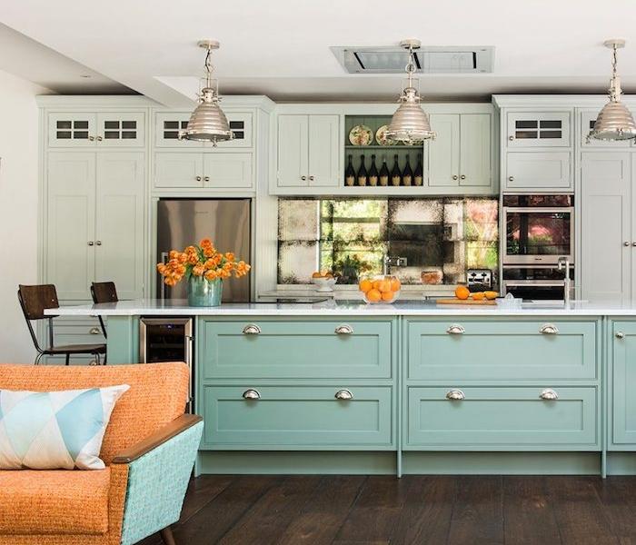 cuisine ouverte sur salon, meuble facade cuisine vert menthe, ilot central vert, parquet marron, suspensions industrielles, canapé bleu et orange