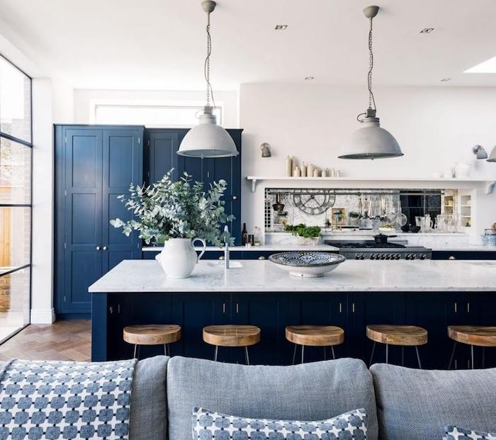 cuisine ouverte sur salon, facade blanche, armoire et ilot central bleu avec plan de travail en mabre, suspensions industrielles, canapé gris