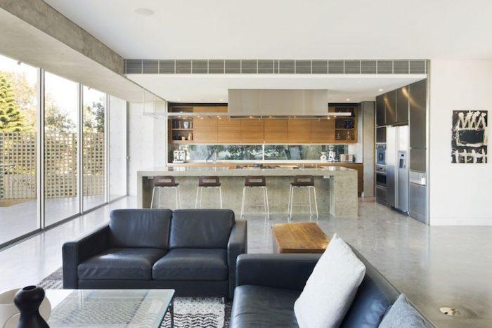 modele de cuisine ouverte sur salon, facade meuble cuisine en bois et bar gris avec des chaises bois et metal, revetement, effet beton, canapé gris, table en verre
