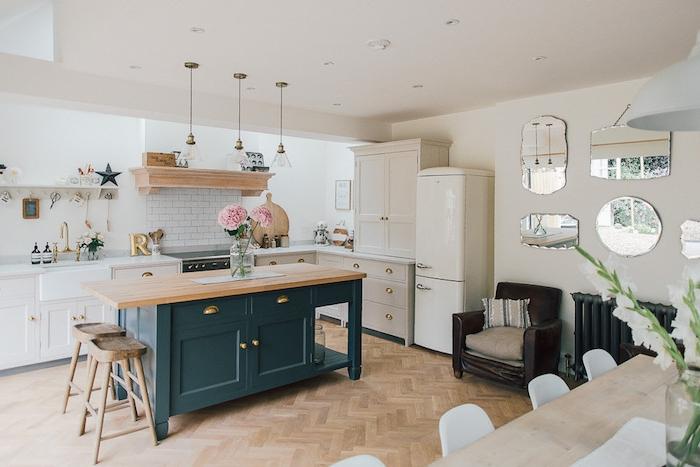 cuisine americaine, style campagne chic, ilot central bleu gris, meuble facade cuisine blanche, parquet clair, salle à manger en table en bois et chaises blanche