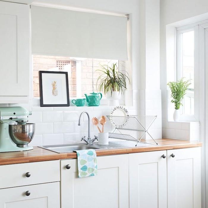cuisine rénovée traditionnelle, style campagne avec facade blanche et plan de travail bois, carrelage blanc, petites plantes vertes