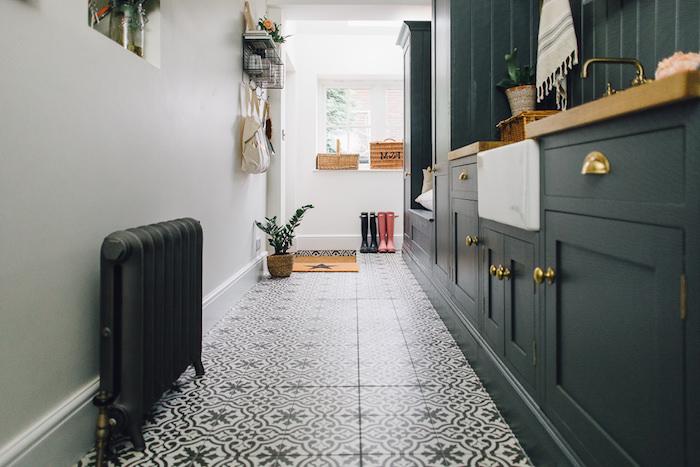 modele de cuisine rénovée noire avec boutons de pote dorés, credence bois noire, carrelage à motifs floraux noir et blanc