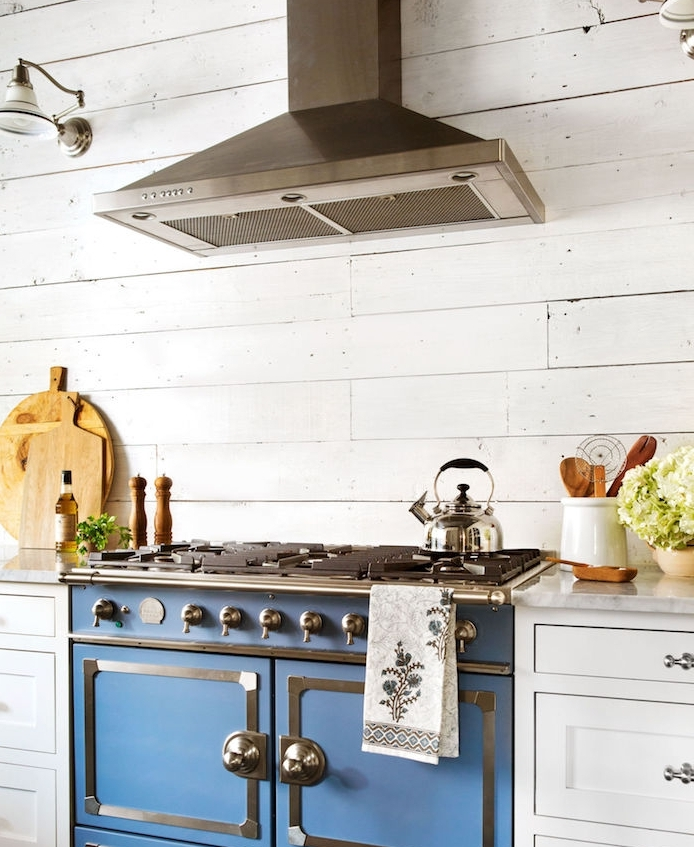 cuisine rustique, style campagne chic avec fourneau à l ancienne, piano de cuisson bleu marine et meuble cuisine blanc, lambris poutres blanches et aspirateur inox
