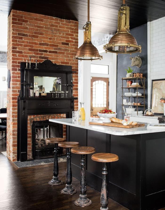 cuisine style campagne avec cheminée en briques, ilot central et pan de mur repeint de peinture ardoise, plan de travail ilo en marbre, suspensions industrielles