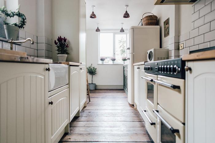cuisine rénovée avec meuble blanc cassé, parquet bois brut et credence en carrelage blanc, plantes vertes