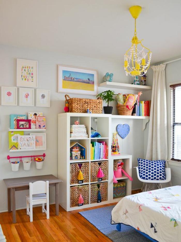 aménager une chambre de 10m2 pour enfant avec meuble blanc de rangement, luminaire en jaune, en style baroque, table basse couleur taupe, avec petite chaise blanche avec dossier haut, fauteuil blanc avec coussin bleu avec pois blancs, des tableaux aux couleurs vives aux murs