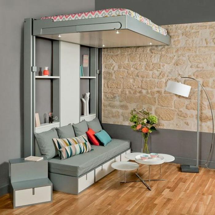 chambre de 9m2 en gris et rose fonction aussi de salon, avec des luminaires sous le lit mezzanine, lampadaire sur pied au sol en métal gris