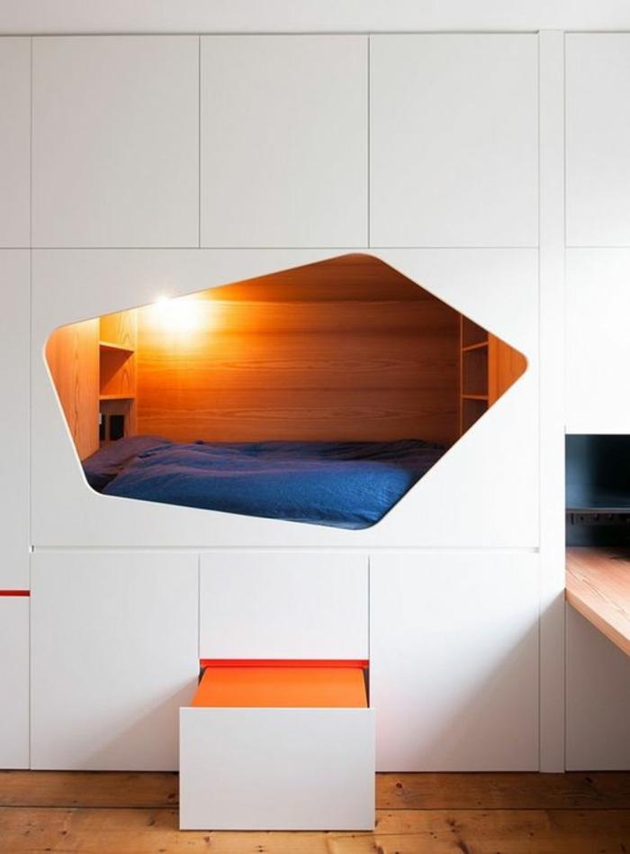 chambre de 9m2 dans une niche en blanc illuminée à l'intérieur, avec plein de tiroirs de rangement autour du lit, système coulissant