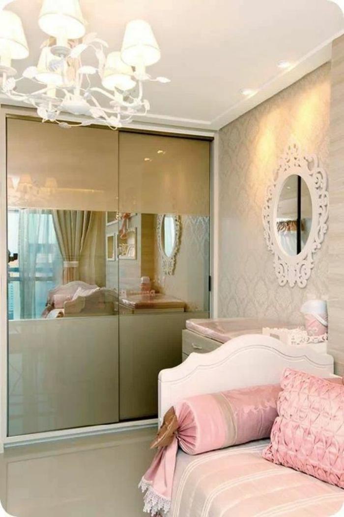 deco petite chambre adulte en style romantique, avec grand lustre, miroir blanc en style baroque, armoire aux portes coulissantes en couleur or, lit blanc avec des coussins roses en forme carrée et en forme de bonbon