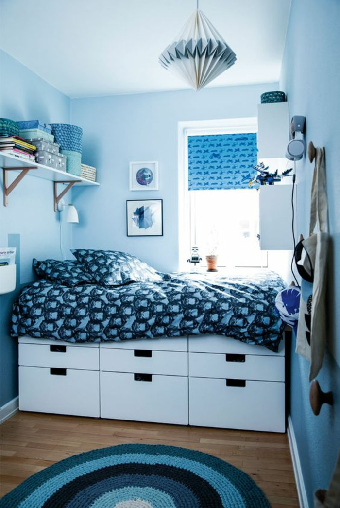 aménager une chambre de 10m2 en bleu azur, lit avec des grands tiroirs en dessous, avec couverture en bleu et blanc, luminaire en carton en bleu et blanc en forme conique, tapis rond en azur, blanc et noir