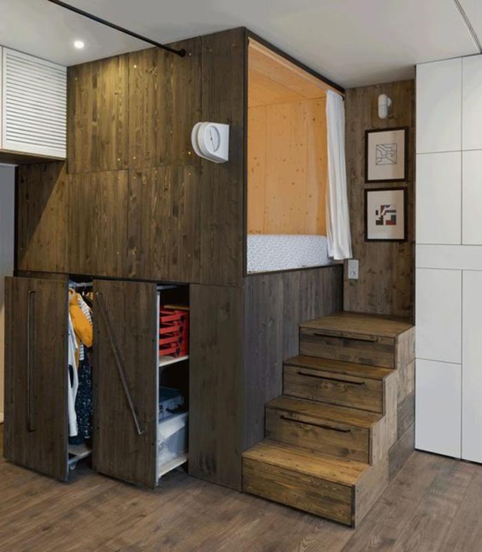 chambre de 9m2 en couleur taupe avec des cases de rangement coulissantes, des escaliers qui servent de rangement, revêtement du sol en taupe, parquet massif