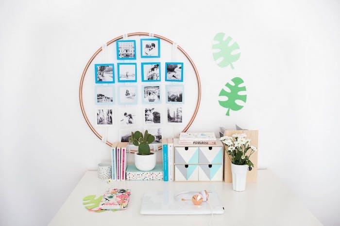 anneau metallique avec des photos noir et blanc sur du papier bleu et blanc suspendus, decoration bureau avec livres, plantes et casiers personnalisés