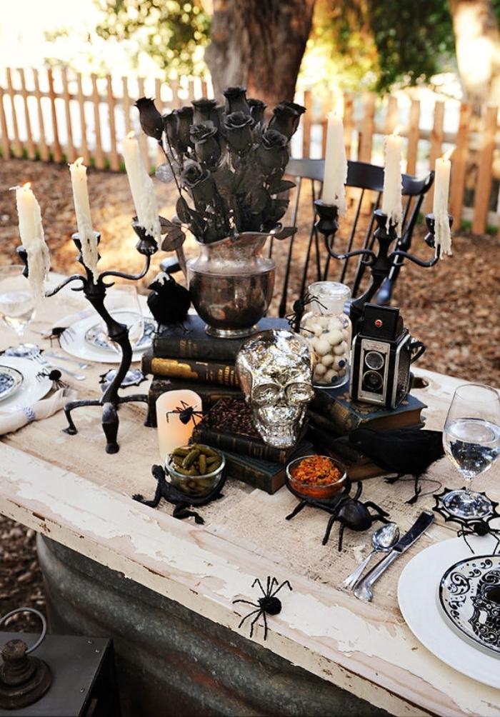 organisation fête Halloween en plein air, table Halloween en blanc et noir avec bougeoirs et crâne en argent