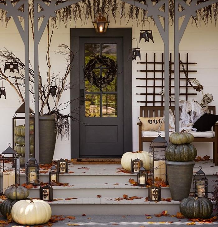 porte d'entrée et véranda de style halloween, citrouilles blanches et grises avec lanternes noires et bougies blanches
