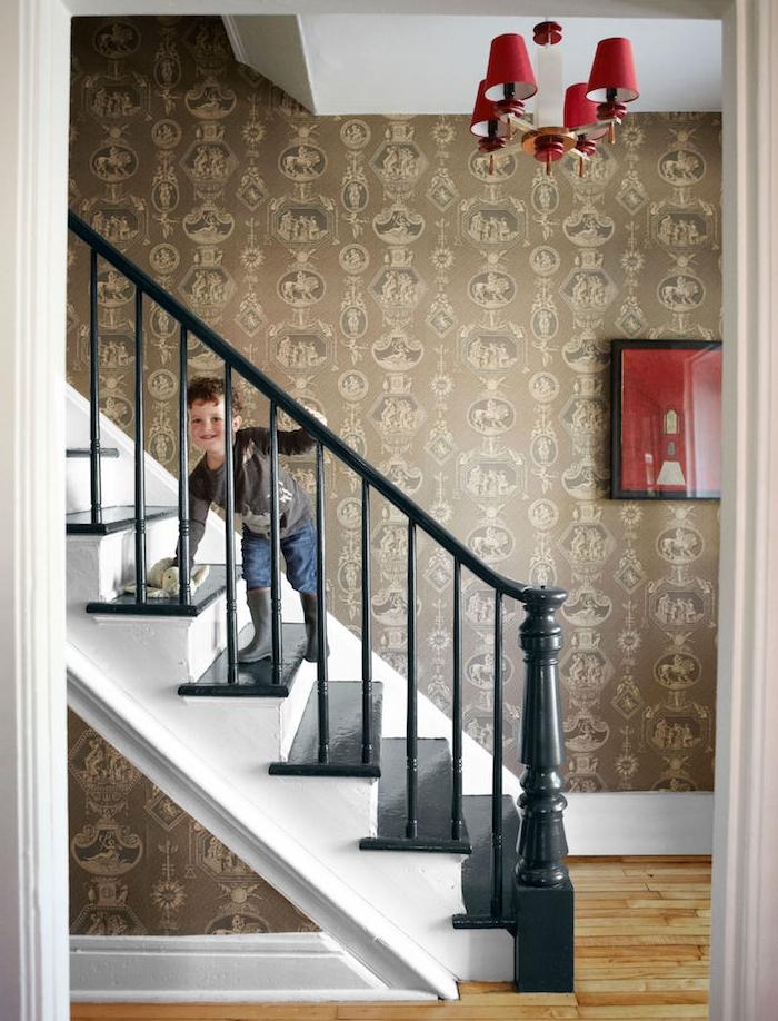 déco montée de escalier avec papier peint marron, gris et beige, style vintage, rambarde escalier et marches repeints en noir, parquet bois clair, accents rouges