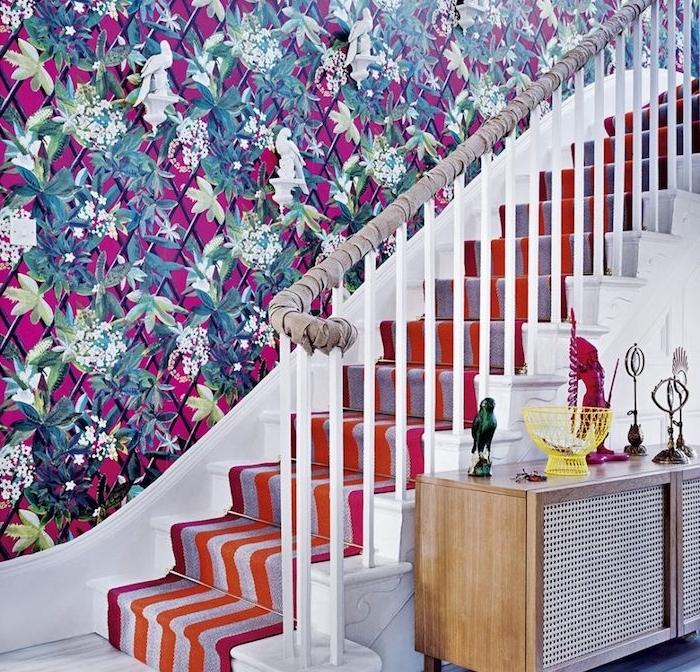 déco montée d escalier avec mur habillé de papier peint à motifs floraux sur un fond fuchsia, habillage escalier de tapis à rayures, orange, rouge, gris et rose, main courante avec tissu gris enveloppé autour