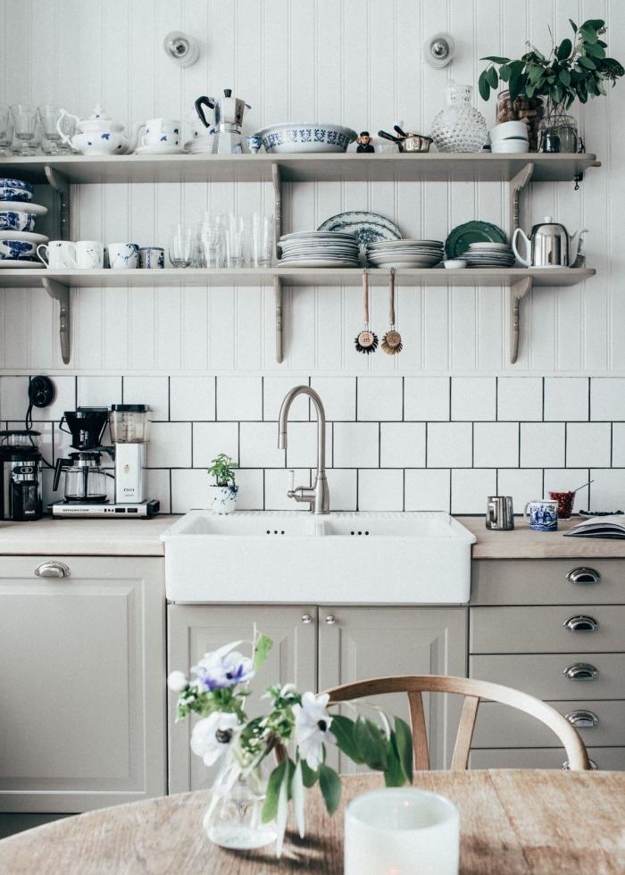 cuisine équipée, rangement horizontale en bois clair avec services de thé et herbes vertes