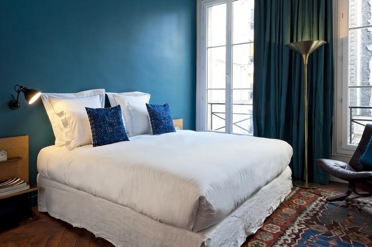 idée déco chambre adulte, mur d accent bleu foncé, rideau bleu paon, linge de lit blanc avec des coussins decoratifs bleus, tapis oriental, parquet marron
