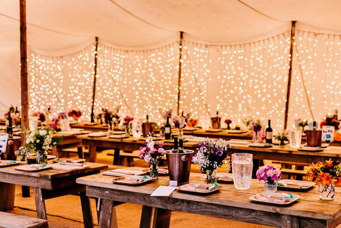 mariage champetre chic, tables et bancs en bois, pots en verre fleuris, décoration de guirlandes lumineuses, chapiteau mariage