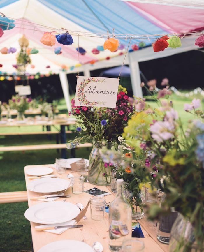 décoration champêtre pour votre mariage, table en bois, assiettes blanches, vases en verre fleuries, deco de fleurs en papier crepon