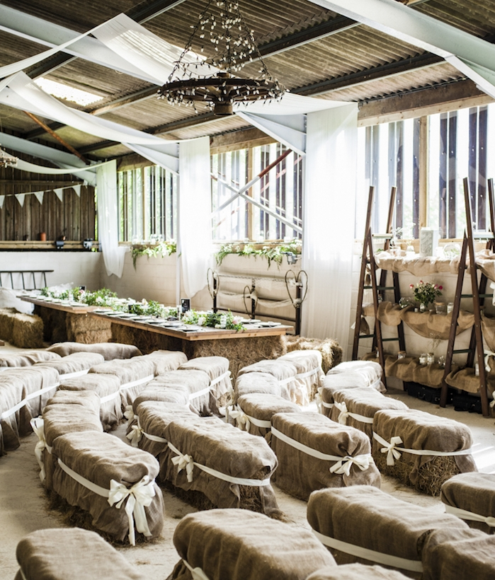 deco mariage champetre, des bancs de meules de foin recouverts de jute, table pieds de foin et plateau en bois, mariage dans une grange