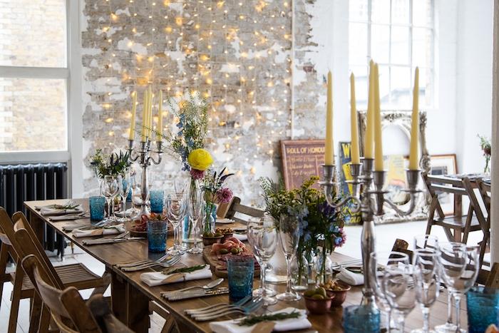 decoration mariage champetre, table et chaises en bois, verres bleues, bouteilles en verre avec des fleurs, bougeoir argenté avec bougies jaunes, guirlande lumineuse sur un mur usé