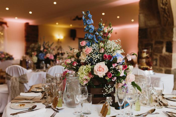bouquet champetre coloré dans une petite cagette bois marron, nappe blanche, composition florale élégante