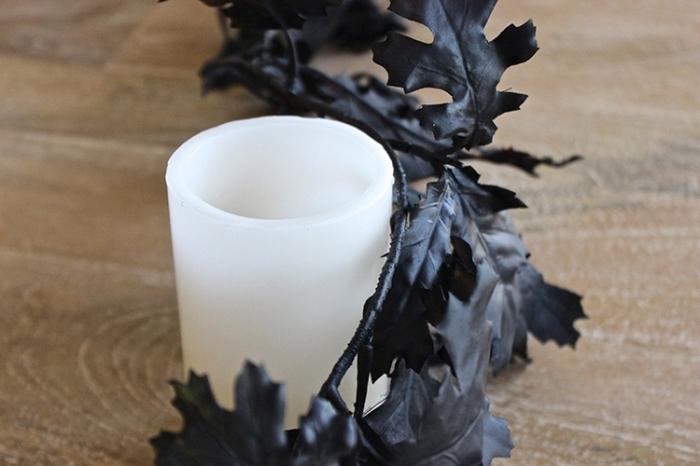 decorer sa maison, table de bois décorée avec bougies blanches et guirlande diy en feuilles peintes noires