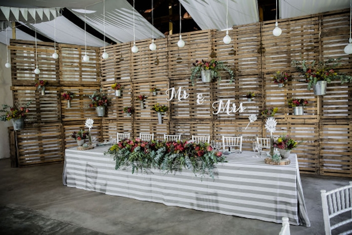 un mur en palettes de bois rustique avec seaux et boites de conserve fleuries, table avec nappe blanche et grise, decoration florale